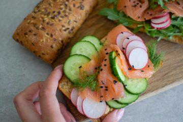 Skrudintos duonos sumuštiniai su humusu, lašiša, agurkais ir ridikėliais